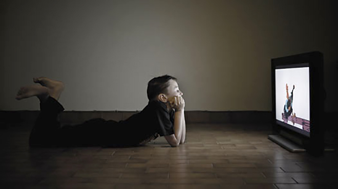 Boy (8-9) lying on floor watching television at night, side view